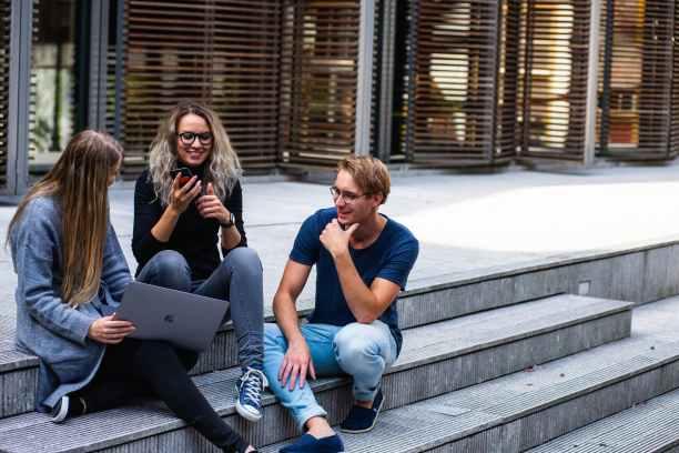 Dvije žene i muškarac sjede na stepenicama i razgovaraju koristeći svoje socijalne vještine.