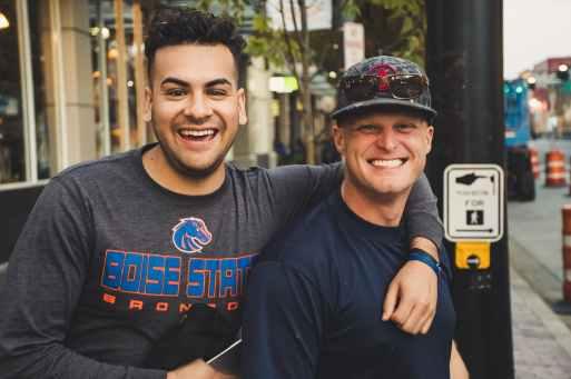 Dvojica muškaraca u vestama stoje zagrljeni na ulici i smiju se u kameru u znak pravog prijateljstva.