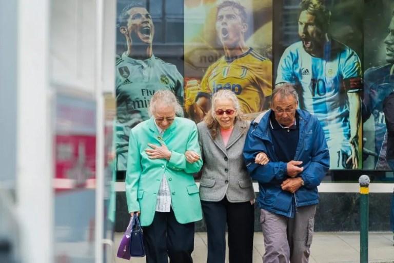 three older people arm in arm