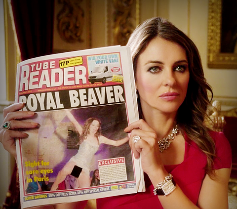 """Queen Helena holds up a newspaper with the headline """"Royal Beaver"""""""