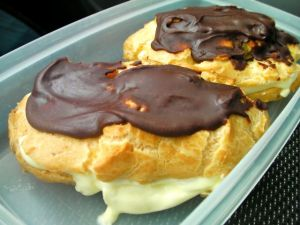 Container with two chocolate glazed cream eclairs