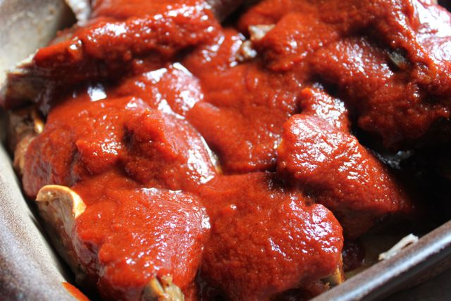 Cooked ribs, just about to go back in the oven, covered in sauce
