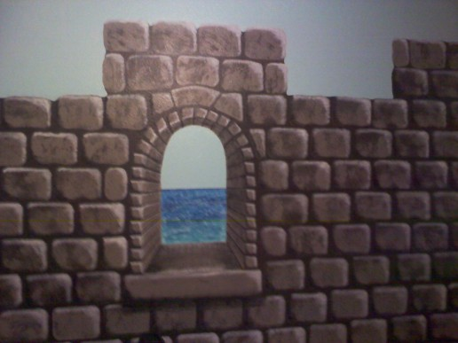 Long shot of the faux castle wall with the ocean showing through the arched window