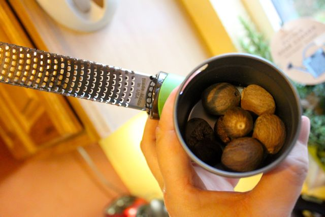 A microplane grater and a tin of whole nutmegs