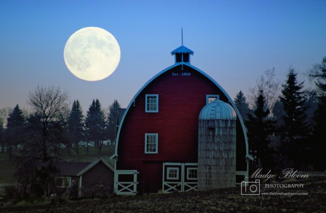 A scene at dusk, with a large moon on the left and a red barn and silo in the foreground