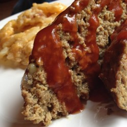 Plate with two slices of meatloaf, glaze dribbling over sides