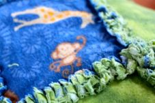 Up close view of a blue monkey-print and solid lime green flannel rag quilt