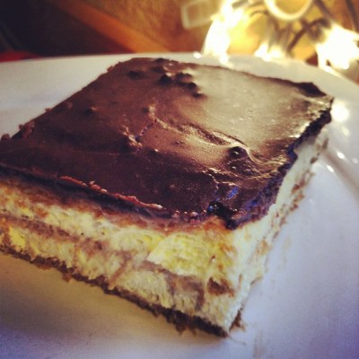Piece of chocolate glazed eclair cake on a white plate