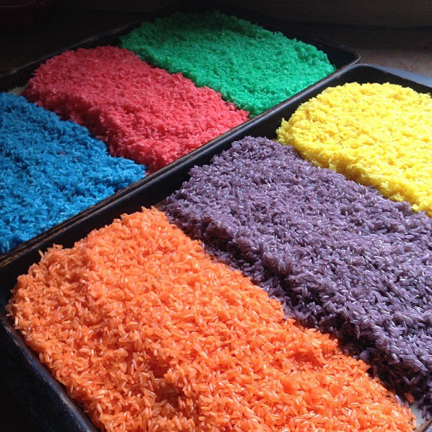 two baking sheets containing three piles of colored rice each