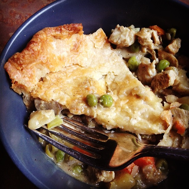 Blue bowl with a slice of chicken pot pie oozing out from under the crust