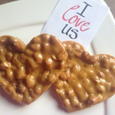 "Two heart-shaped peanut brittle ""cookies"" on a white plate with a note that reads, ""I love us."""