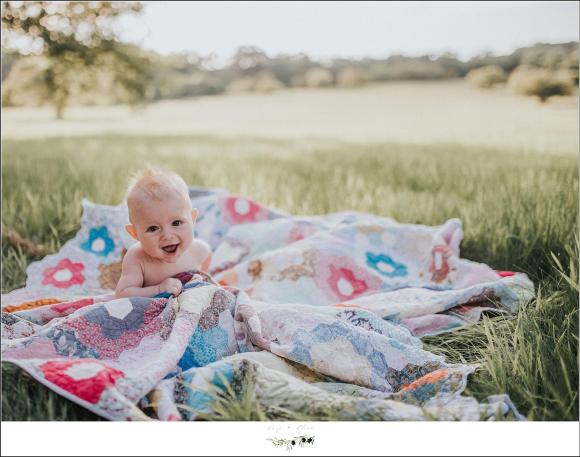 Baby on a blanket in a field