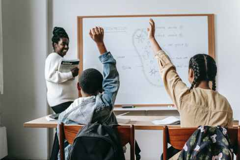 black woman with pupils in classroom, she is teaching
