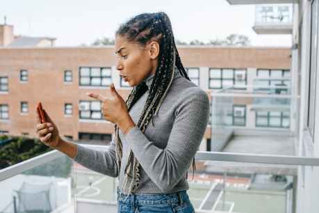mad ethnic female gesticulating while having video conversation on smartphone on terrace A sour apple.