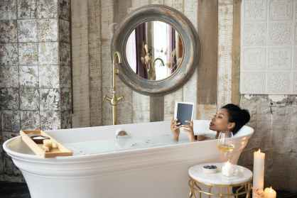 black woman reading book while taking bath self-care is part of my new growth mindset