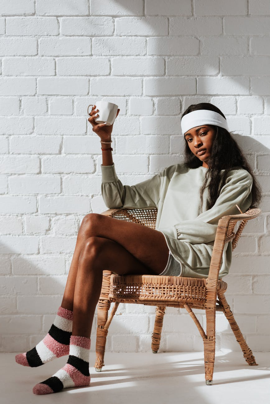 black woman with cup of drink resting in armchair indoors