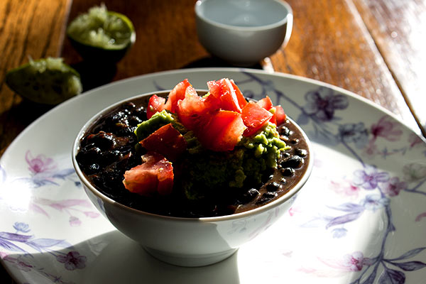 bowl of stewed black beans with guacamole
