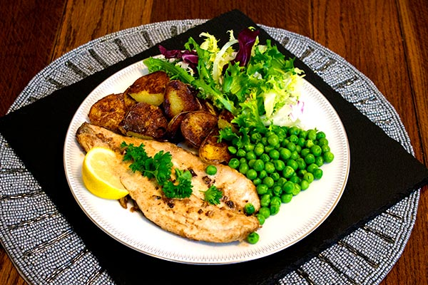 sea bass fillet fried in brown butter, garlic and lemon, with pan-fried potato, peas and salad.
