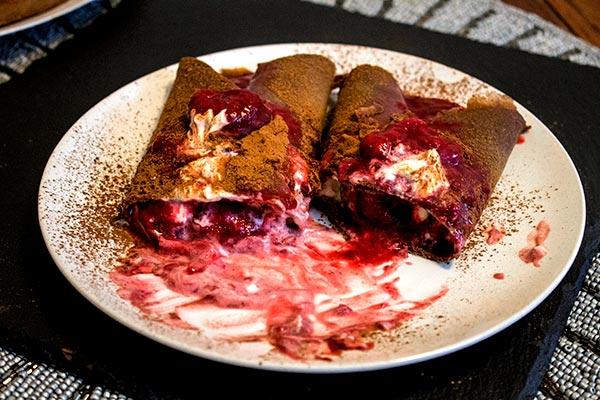 chocolate pancakes with stewed ginger strawberries and raspberries and vanilla yoghurt cream