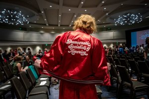 """A person wearing a stylish red jacket that says """"Democratic Socialists of America"""" on the back."""