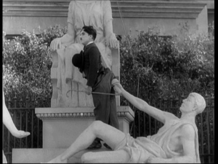 Scene from the Movie where The Tramp is facing away from a lying down statue and has his rear is placed against the outstretched arm of the statue