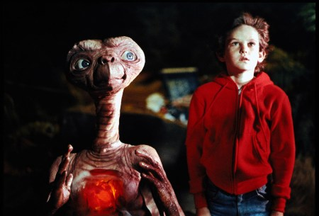 E.T. going home. E.T. and Elliot both facing the camera. It appears that E.T. is holding his hands apart with his heart in the middle. Both are looking up at the spaceship.