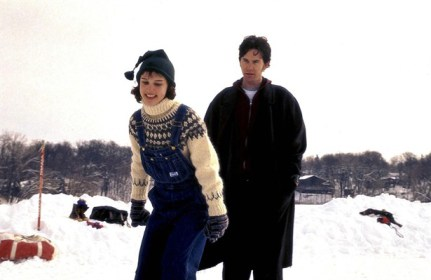 In the snow, Natalie in the forefront being playful in her snowsuit, sweater,and hat. Tim Robbins is standing behind her. Snow everywhere on the ground!!!!