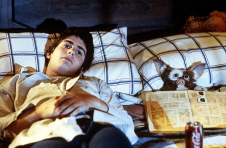 Zach Galligan (teen boy) and Gizmo (Mogwai) are lying in bed presumably staring at a TV screen. For some reason, what appears to be a book is open and spread across Gizmo.