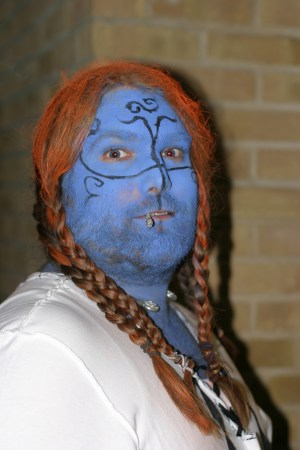 LARPER with a short beard, skin painted blue, with long red braids