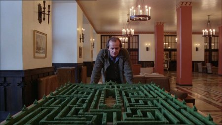 Nicholson leadning over a maze atop a table in the lobby of the hotel.