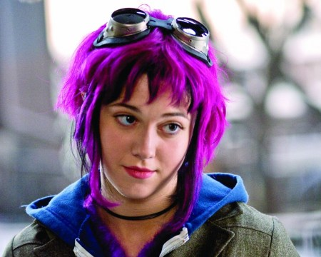 Mary Elizabeth Winstead as Ramona Flowers from the 2010 film, Scott Pilgrim Vs. The World , she has purple hair, aviator goggles resting atop her head, and a blue hoodie under a khaki pea coat.