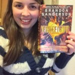 Reviewer Mariah Kaercher, smiling, with a copy of Firefight by Brandon Sanderson