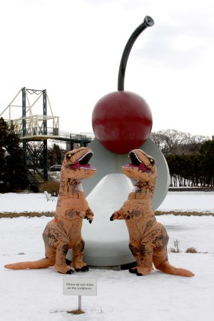 Two T-Rexes pose by the Spoonbridge and Cherry statue