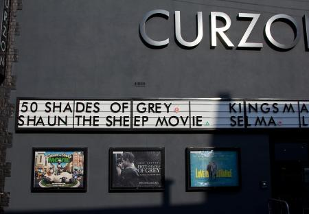 A movie theater show board listing Fifty Shades of Grey above Shaun the Sheep Movie