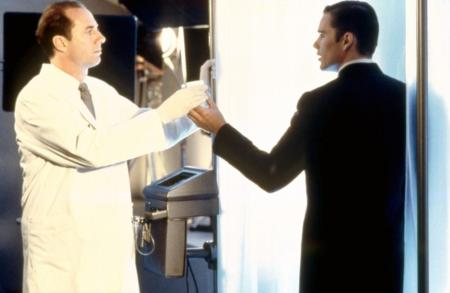 GATTACA, Xander Berkeley, Ethan Hawke, 1997, (c)Columbia Tristar Ethan is in a black suit going through a bright door.