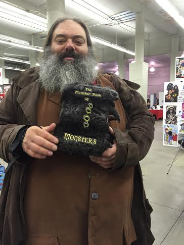 "Awesome Hagrid cosplay, a man with a large grey beard, dressed in a brown shirt and coat, with a furry book that has four eyes on it's cover, claws on it's sides, and teeth at the opening of the book, it is titled ""The Monster Book of Monsters""."
