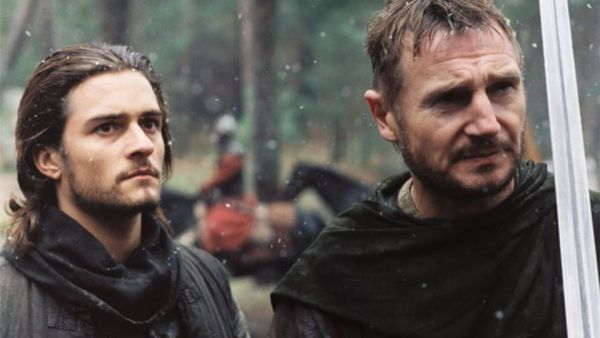 Bloom and Neeson as son and father clearly outside, looking grim in their dark garb.