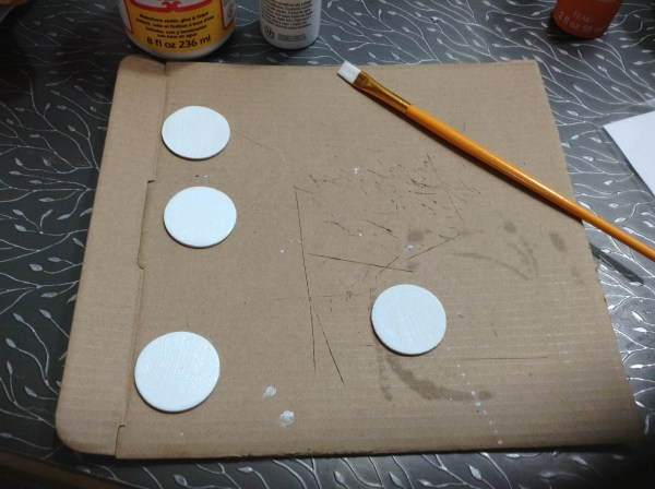 Painting the base color on the medallion.