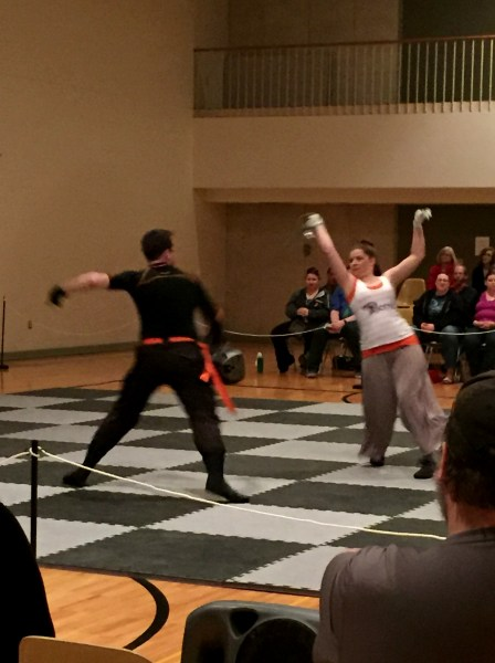 Phoenix teammates, David Elwyn, representing the black team, and Jenna Young, representing the white team, battle for the square using dueling sabers.