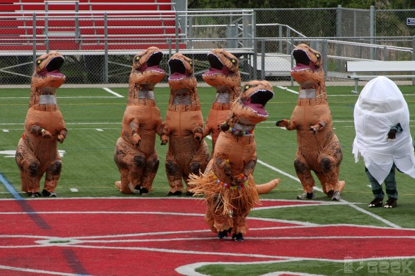 A group of humans in inflatable T-Rex costumes dance on a football field. One T-Rex is wearing a hula skirt, and another is hatching out of its egg.