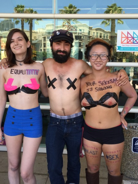Three topless people standing in a line with their arms around each other and tape over their nipples protest against sexual harassment and the oppression of women's bodies.