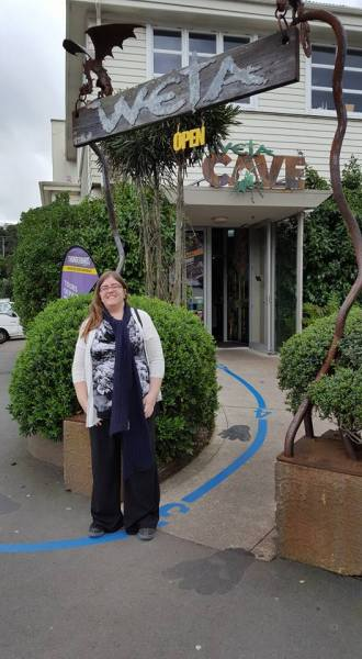 Katy standing under the Weta Cave entrance signage