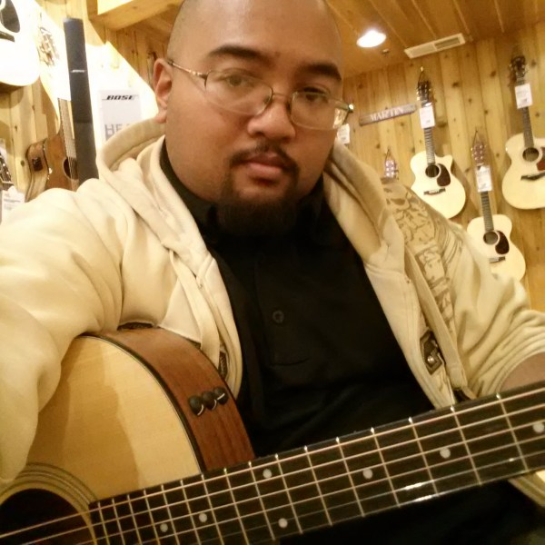 Author poses with a Taylor acoustic guitar at a Guitar Center.