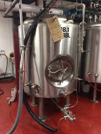 Large silver fermenter in the basement of Clockwerks Brewing