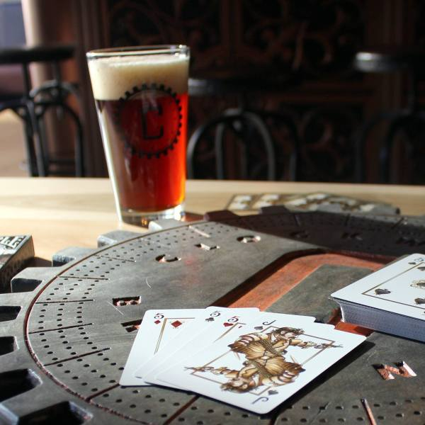Side view of a cribbage board, with cards laid out on top. In the background is a full glass of beer, with the Clockwerks Brewing logo on the glass.