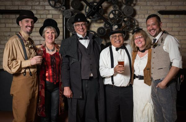 Six people dressed in steampunk clothes are posed in front of a gear sculpture. Several people are holding beers and toasting the photographer.