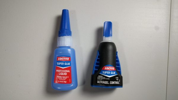 An image with two separate bottles of Loctite superglue.
