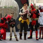 Cosplayers dressed as Squirrel Girl and Deadpool pretend to play cards