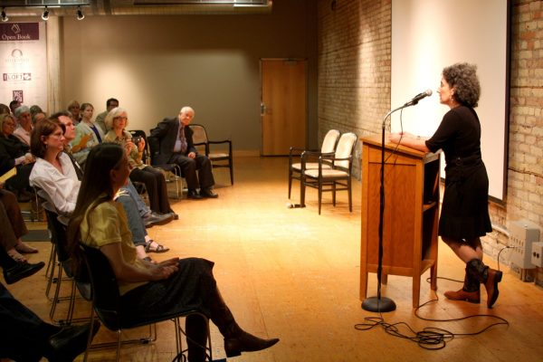 A woman at a podium reads to a seated audience