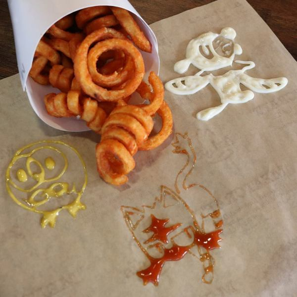A bag of curly fries next to drawings of Pokémon in condiments